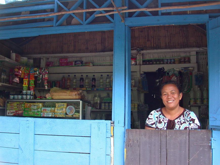 Fara est tout sourire devant sa petite boutique d'Ylang Ylang